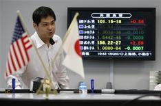 An employee of a foreign exchange trading company works next to a monitor displaying the Japanese yen's exchange rate against the U.S. dollar (top) and other major foreign currencies in Tokyo May 10, 2013. REUTERS/Issei Kato