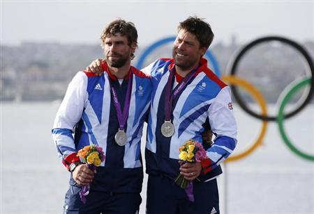 Silver medallists Britain's skipper Iain Percy and crew Andrew Simpson (R) smile during their men's star class keelboat sailing medal race victory ceremony at the London 2012 Olympic Games in Weymouth and Portland, southern England August 5, 2012. REUTERS/Pascal Lauener