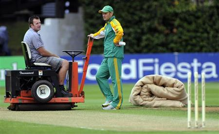 South Africa's coach Gary Kirsten talks to a groundsman as rain delays the start of play against New Zealand in the third and final international test cricket match of the series in Wellington, March 23, 2012. REUTERS/Anthony Phelps/Files