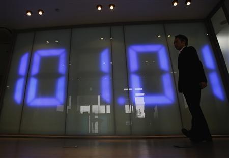 An employee of a foreign exchange company walks past a monitor displaying the Japanese yen's exchange rate against the U.S. dollar in Tokyo May 10, 2013. REUTERS/Toru Hanai
