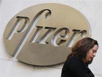 A woman walks past the Pfizer Inc. headquarters in New York, January 31, 2013. REUTERS/Brendan McDermid