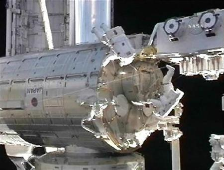 Astronauts Tom Marshburn (top) and Chris Cassidy (R) work during their spacewalk from the International Space Station, in this image from NASA TV July 27, 2009. REUTERS/NASA/Handout