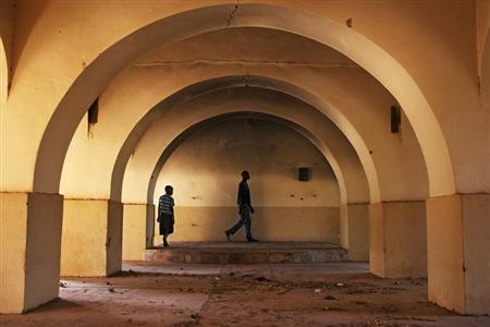 Agali Ag Illa (R), 20, and his brother Mohamed, 7, walk across the former altar of the Catholic church in Gao, Mali March 10, 2013. REUTERS/Joe Penney