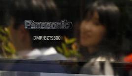 Transeunte é refletida em um produto da Panasonic em uma loja de eletrônicos em Tóquio. A empresa de eletrônicos estimou que seu lucro operacional subirá 55 por cento no ano fiscal que termina em 31 de março enquanto se recupera das fracas operações em TV e outros aparelhos em favor da venda de máquinas, componentes eletrônicos e outros negócios. 09/03/2013 REUTERS/Toru Hanai