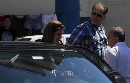 Cuban agent Rene Gonzalez (C) and his wife Olga Salanueva walk outside the U.S. diplomatic mission in Cuba, the U.S. Interests Section (USINT) in Havana May 6, 2013. REUTERS/Enrique De La Osa