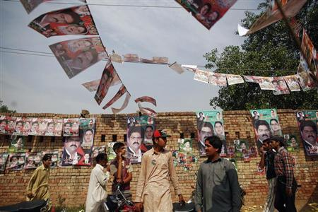 People gather near a polling station in a village near Lahore May 11, 2013. REUTERS/Damir Sagolj