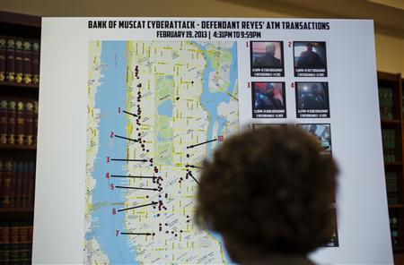 A woman looks at a map showing where eight members belonging to a New York-based cell of a global cyber criminal organization withdrew money from ATM machines, during a news conference in New York, May 9, 2013. REUTERS/Lucas Jackson