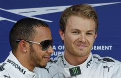 O piloto da Fórmula Um alemão Nico Rosberg sorri ao lado do parceiro britânico Lewis Hamilton (esquerda) após corrida no Circuito de Catalunha, próximo a Barcelona, Espanha. 11/05/2013 REUTERS/Albert Gea