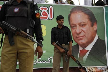Policemen guard near the portrait of Nawaz Sharif, leader of political party Pakistan Muslim League-Nawaz (PML-N), during an election campaign rally in Peshawar May 7, 2013. REUTERS/Fayaz Aziz