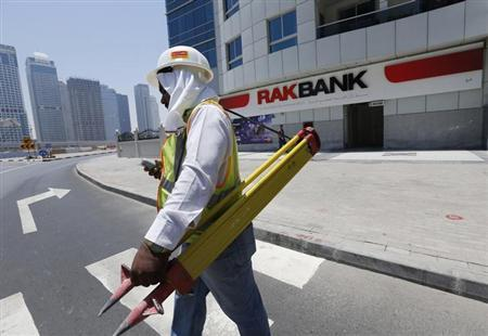 A worker walks past a National Bank of Ras Al Khaimah (RAKBANK) branch at Dubai Marina in Dubai May 12, 2013. REUTERS/Ahmed Jadallah