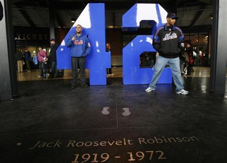 Fans pose with Jackie Robinson's number in the Jackie Robinson Rotunda during an MLB exhibition game between the New York Mets and the Boston Red Sox at Citi Field in Flushing, New York April 3, 2009. REUTERS/Lucas Jackson/Files