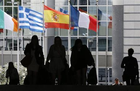 Pedestrians walk towards the (L-R) Irish, Greek, Spanish and French national flags outside the European Parliament in Brussels May 3, 2013. REUTERS/Francois Lenoir