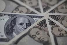 """Купюры валют иена и доллар США в Токио 28 февраля 2013 года. Иена упала ниже 102 за доллар в понедельник, после того как Японии удалось избежать прямой критики агрессивной программы монетарного смягчения на саммите """"Большой семерки"""" на выходных. REUTERS/Shohei Miyano"""