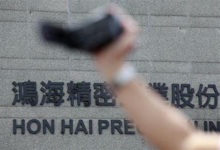 A police officer films a protest outside the Hong Hai headquarters in Tucheng, Taipei, May 28, 2010. REUTERS/Nicky Loh