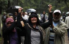 Родственники оплакивают убитого взрывами автомашин в турецком городе Рейханлы у границы с Сирией 12 мая 2013 года. Турция обвинила связанную с сирийской разведкой организацию в проведении взрывов, ставших причиной гибели 46 человек в пограничном турецком городе, заявив в воскресенье, что для мирового сообщества настало время предпринять действия против правительства Башара Асада. REUTERS/Umit Bektas