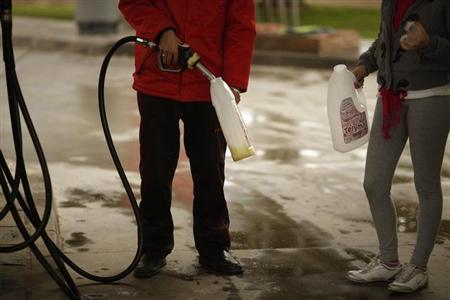 A worker pumps petrol into a customer's plastic bottles at a petrol station in Cuevas del Becerro, near Malaga, southern Spain March 4, 2011. REUTERS/Jon Nazca/Files