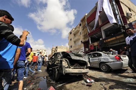 Onlookers take photographs following a car bomb explosion outside a hospital in Benghazi May 13, 2013. REUTERS/Esam Al-Fetori