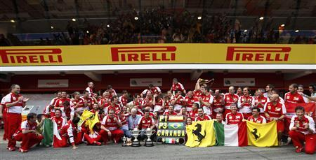 The Ferrari Formula One team pose for photographers with their trophies after drivers Fernando Alonso of Spain and Felipe Massa of Brazil won first and third place respectively in the Spanish F1 Grand Prix at the Circuit de Catalunya in Montmelo, near Barcelona, May 12, 2013. REUTERS/Gustau Nacarino