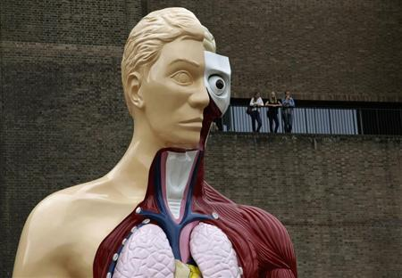 Visitors stand at a balcony behind the Damien Hirst sculpture ''Hymn'' outside the Tate Modern gallery in London August 21, 2012. REUTERS/Stefan Wermuth