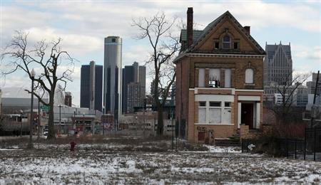 A vacant, boarded up house is seen in the once thriving Brush Park neighborhood with the downtown Detroit skyline behind it in Detroit, Michigan March 3, 2013. REUTERS/ Rebecca Cook