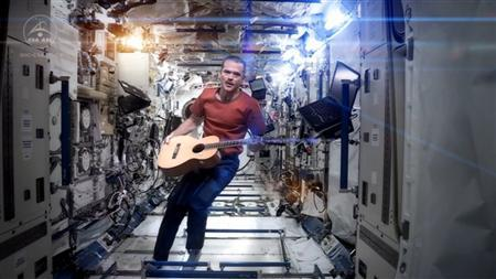 Canadian astronaut and International Space Station (ISS) Commander Chris Hadfield performs his zero-gravity version of David Bowie's hit ''Space Oddity'' in this image taken from video, courtesy of Chris Hadfield, NASA and CSA. The video, with its familiar refrain ''Ground Control to Major Tom,'' had more than 1.5 million hits on YouTube early afternoon on May 13, 2013, and was being touted as the first music video ever filmed in space. REUTERS/Chris Hadfield, NASA and CSA/Handout via Reuters