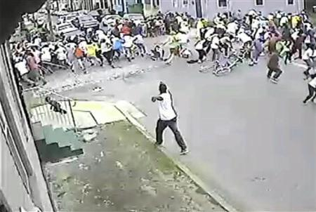 A still image taken from security camera video released by the New Orleans Police Department (NOPD) shows a gunman shooting into a crowd gathered for a Mother's Day second line parade in New Orleans, Louisiana May 12, 2013. REUTERS/NOPD8th/Handout via Reuters