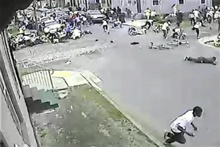 A still image taken from security camera video released by the New Orleans Police Department (NOPD) shows a gunman (bottom R) running away after shooting into a crowd gathered for a Mother's Day second line parade in New Orleans, Louisiana May 12, 2013. REUTERS/NOPD8th/Handout via Reuters