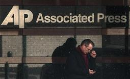 A man looks down at his smartphone as he walks past the offices of the Associated Press in Manhattan, New York May 13, 2013. REUTERS/Adrees Latif