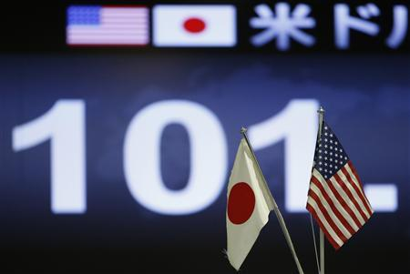 A monitor displaying the Japanese yen's exchange rate against the U.S. dollar is seen through the U.S. and Japanese national flags at a foreign exchange trading company in Tokyo May 13, 2013. REUTERS/Issei Kato