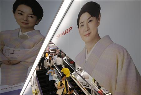 People ride an escalator past Japanese display maker Sharp Corp's advertisements at an electronics retail store in Tokyo May 14, 2013. REUTERS/Toru Hanai