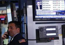 Трейдер звонит по телефону в торговом зале Нью-Йоркской фондовой биржи, 13 мая 2013 года. Американские акции завершили торги понедельника практически без изменений, приостановившись после стремительного ралли, но хорошие показатели акций сектора здравоохранения ограничили спад. REUTERS/Brendan McDermid