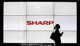 Женщина проходит мимо логотипа Sharp Corp. на ж/д станции в Токио, 6 марта 2013 года. Sharp Corp, поставщик дисплеев для Apple Inc, намерен увеличить продажи комплектующих главному конкуренту американской компании - корейской Samsung Electronics Co. REUTERS/Yuya Shino