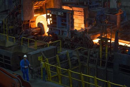 A worker stands in front of a rolling mill in the ArcelorMittal steel factory in Eisenhuettenstadt, 124 km (77 miles) east of Berlin November 26, 2012. REUTERS/Thomas Peter