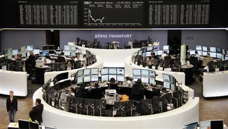 Traders work at their desks in front of the DAX board at the Frankfurt stock exchange May 14, 2013. REUTERS/Remote/Lizza David