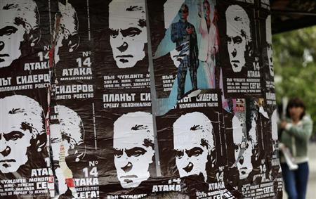 A woman walks past election posters of Volen Siderov, leader of the Attack party, in Sofia May 13, 2013. REUTERS/Stoyan Nenov