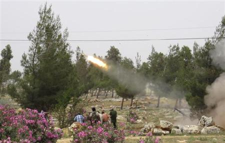 Free Syrian Army fighters react during the firing of a rocket after what activists said was clashes between government forces and the Free Syrian Army in Binnish in Idlib province May 9, 2013. Picture taken May 9, 2013. REUTERS/Mohamed Kaddoor
