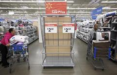 Покупатели в магазине Walmart Store в Чикаго 23 ноября 2012 года. Жесткая бюджетная политика сократит экономический рост США в текущем квартале, прежде чем он ускорится во втором полугодии, заставляя Федрезерв продолжать скупку облигаций как минимум до 2014 года, показал опрос Рейтер. REUTERS/John Gress