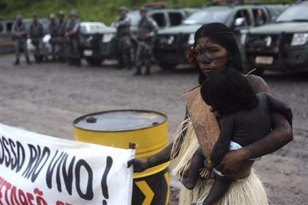 An Indian woman cradles her child while holding a banner in front of police, as Amazon Indians from different tribes hold a meeting with a government envoy to discuss a proposal to end their occupation of the Belo Monte hydroelectric dam construction site, in Vitoria do Xingu, near Altamira in Para State, May 8, 2013. REUTERS/Lunae Parracho