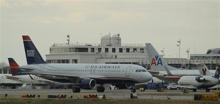 US Airways jets taxi past a parked American Airlines jet (C) at Reagan National Airport in Washington February 28, 2013. REUTERS/Gary Cameron