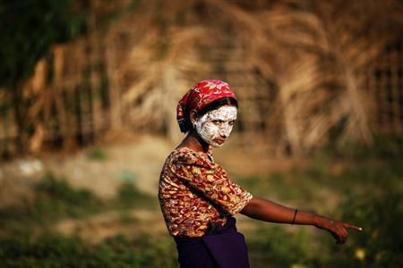A Rohingya Muslim woman wearing traditional thanaka paste on her face gestures in a camp for people displaced by violence, near Sittwe April 26, 2013. REUTERS/Damir Sagolj