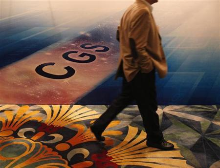 A man walks past a backdrop to China Galaxy Securities' investor presentation for their global offering in Hong Kong May 7, 2013. REUTERS/Bobby Yip