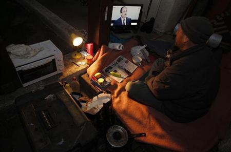 A homeless man named Didier watches French President Francois Hollande on France 2 television in Andernos, southwestern France, March 28, 2013. REUTERS/Regis Duvignau