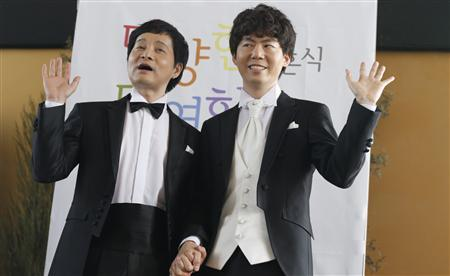 Gay South Korean film director Kim Jho Gwang-soo (L) and his partner Kim Seung-hwan pose during a news conference in Seoul May 15, 2013. REUTERS/Lee Jae-Won