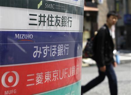 A man walks past a signboard of Japan's three mega banks, Sumitomo Mitsui Banking Corporation (top), Mizuho Bank (C) and Bank of Tokyo-Mitsubishi UFJ, in Tokyo May 15, 2013. REUTERS/Toru Hanai