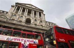 Автобусы проезжают мимо Банка Англии в Лондоне, 23 февраля 2013 года.Банк Англии в среду изменил привычной тенденции, немного повысив прогноз роста и предположив быстрое замедление инфляции. REUTERS/Neil Hall