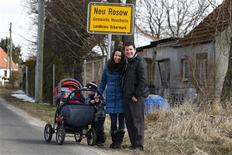 Pawel Pilsniak, his wife Anna and two children Micheasz and Nathan pose for a photograph by the entrance to the village of Neu Rosow, Germany located near the Polish border April 6, 2013. REUTERS/Peter Andrews