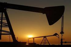 Оборудование для добычи нефти виднеется в лучах восходящего солнца на месторождении в Баку 24 января 2013 года. Чистая прибыль банков богатого нефтью Азербайджана удвоилась за год до $90,7 млн. REUTERS/David Mdzinarishvili
