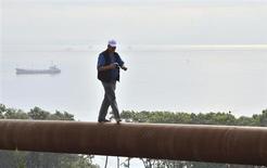 Человек идет по газовой трубе на острове Русский близ Владивостока 23 августа 2011 года. Газпром готов предложить иностранным партнерам до половины в капитале проекта по сжижению газа во Владивостоке, сказал на конференции зампред правления Виталий Маркелов. REUTERS/Yuri Maltsev