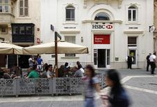 People sit in an outdoor coffee shop in front of an HSBC bank branch in Valletta May 8, 2013. REUTERS/Darrin Zammit Lupi