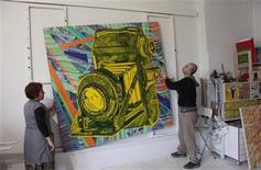 Turkish artist Yigit Yazici (R) fixes one of his artworks at his studio in Istanbul April 17, 2013. REUTERS/Murad Sezer